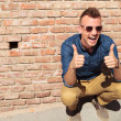 Casual man thumbs up by wall — Stock Photo #25737039