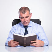 Senior business man reads at his desk — Stock Photo