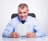 Senior business man smiles at his tablet — Stock Photo