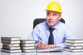 Old engineer writes at desk while pondering — Stock Photo