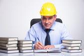 Vecchio uomo d'affari scrive alla scrivania piena di libri — Foto Stock