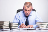 Old business man writes at his desk — Stock Photo