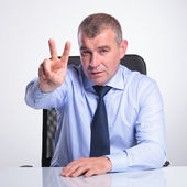 Senior man shows victory from desk — Stock Photo