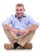 Casual middle aged man sits and smiles — Stock Photo