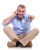 Casual middle aged man sits talks and points — Stock Photo