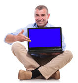 Casual old man sits and presents his laptop — Stock Photo