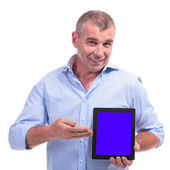 Casual middle aged man presenting tablet — Stock Photo