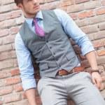 Casual man poses at a brick wall — Stock Photo #26914893