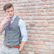 Casual man smoking by brick wall — Stockfoto