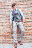 Casual man leans on a brick wall with his back — Stock Photo