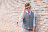 Casual man leans on wall and adjust sunglasses — Stock Photo
