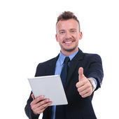 Business man holds tablet and shows thumb up — Stock Photo