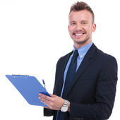Business man smiles with pen and clipboard — Stok fotoğraf