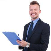 Business mann lächelt mit stift und zwischenablage — Stockfoto