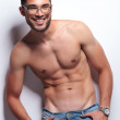 Постер, плакат: Topless young man with thumbs in loops