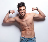 Topless young man showing off with biceps — Stock Photo