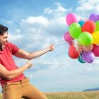 Casual man with colorful balloons — Stock Photo