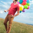 Stock Photo: Casual mwith baloons looks back