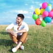 Casual man with balloons sits on grass and smiles — Stock Photo #30364821