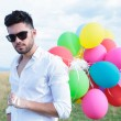 Closeup of casual man with balloons and sunglasses — Stock Photo