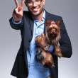 Casual young man holds puppy and shows victory — Stock Photo #30365035