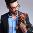 Casual young man looks at puppy — Stock Photo