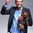 Stock Photo: Casual young man holds puppy and shoots with hand