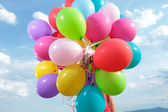 Bunch of balloons held by a man outdoor — Stock Photo
