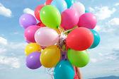 Manojo de globos sostenido por un hombre al aire libre — Foto de Stock