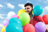 Casual man with baloons all over him — Stock Photo