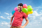 Casual man with balloons and hands on hips — Stock Photo