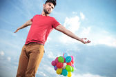 Casual man with balloons looks to his side — Stock Photo