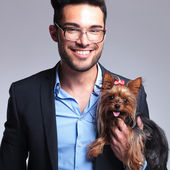 Casual young man holds puppy and smiles — Stock Photo