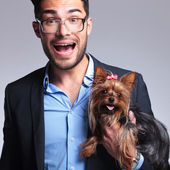 Surprised young man holds puppy — Stock Photo