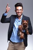 Casual young man holds puppy and shoots with hand — Stock Photo