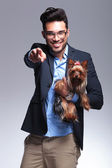 Casual young man holds puppy and points at you — Stock Photo