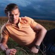 Casual man looks frowned at you, while laying in grass — Stock Photo #31404965