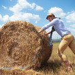 Casual man outdoor pushes a haystack — Stock Photo