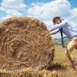 Casual man outdoor looks at you and pushes haystack — Stock Photo