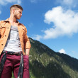 Stock Photo: Casual mfrom mountains looks away with hand in pocket