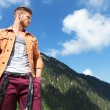 Casual man from mountains looks away with hand in pocket — Stock Photo