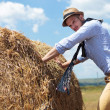 Casual man outdoor pushing a big round haystack — Stock Photo