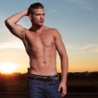 Topless man holds back his hair at sunset — Stock Photo #31407729