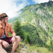 Casual man looks back at mountain — Stock Photo