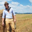Casual man posing next to haystack — Stock Photo