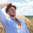 Casual man outdoor leaning back on haystack — Stock Photo