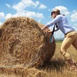 Casual man outdoor pushing a haystack — Stock Photo