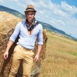 Casual man posing on the field, next to haystack — Stock Photo