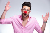 Fashion young man with red nose makes gesture — Stock Photo