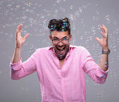 Young fashion man goes crazy among bubbles — Stock Photo